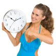 Smiling young woman in swimsuit pointing on clock — Stock Photo #23414246
