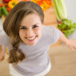 Portrait of happy young woman in kitchen — Stock Photo #23414302