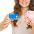 Closeup on woman holding credit card and piggy bank — Stock Photo #23415226