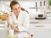 Thoughtful young woman in bathrobe eating breakfast in kitchen — Stock Photo