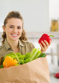 Happy young housewife examines purchases after shopping in kitch — Stock Photo