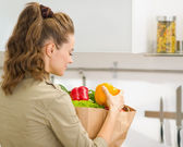 Young housewife examines purchases after shopping in kitchen. re — Stock Photo
