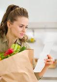 Joven ama de casa examina verificación después de ir de compras — Foto de Stock