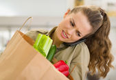 Concerned young housewife with big shopping bag talking mobile p — Stock Photo