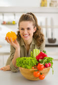 Portrait of happy young housewife with plate of fresh vegetables — Stockfoto