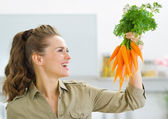 Happy young housewife holding carrots in kitchen — Stock Photo