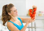 Mutfakta domates sürü tutan mutlu genç kadın — Stok fotoğraf