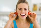 Smiling young woman using cherry tomato as earrings — Stock Photo