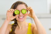 Smiling young woman holding slices of cucumber in front of eyes — Stock Photo