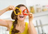 Mujer joven divertida mostrando rodajas de pimiento — Foto de Stock