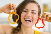 Happy young woman using slice of bell pepper as earrings — Stock Photo