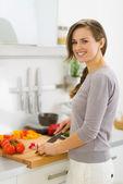 Lächelnde junge hausfrau schneiden gemüse auf salat in küche — Stockfoto
