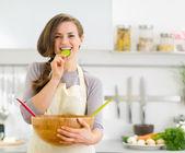 Gelukkig jonge huisvrouw proeverij plakje komkommer van plantaardige s — Stockfoto