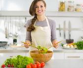Gelukkig jonge huisvrouw mengen plantaardige salade — Stockfoto