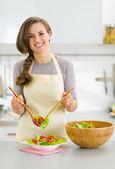 Gelukkig jonge huisvrouw plaat geserveerd met verse groenten salade in — Stockfoto