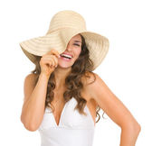 Smiling young woman in swimsuit playing with hat — Stock Photo