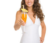 Closeup on young woman in swimsuit giving cocktail — Stock Photo