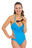 Smiling young woman in swimsuit with sunglasses — Stock Photo