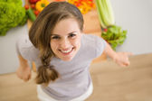 Portrait of happy young woman in kitchen — Stock Photo
