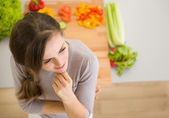 Portrait of thoughtful young woman in kitchen — Stock Photo