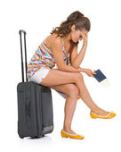 Stressed young tourist woman sitting on wheel bag — Stock Photo