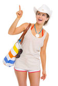 Smiling young beach woman in hat pointing on copy space — Stock Photo