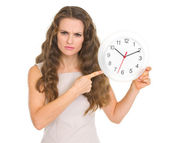 Concerned young woman pointing on clock — Stock Photo