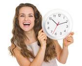 Glad ung kvinna visar klocka — Stockfoto