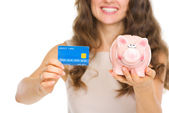 Closeup on woman holding credit card and piggy bank — Stock Photo
