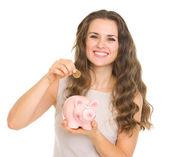 貯金箱にコインを入れて幸せな若い女 — ストック写真