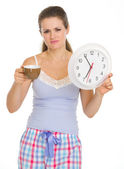 Frustrated young woman in pajamas with cup and clock — Stock Photo