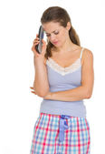 Frustrated young woman in pajamas with tv remote control — Stock Photo