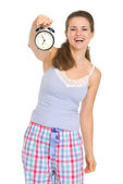 Happy young woman in pajamas showing alarm clock — Stock Photo