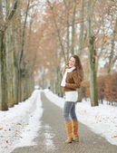 Happy young woman walking in winter park — Stock Photo