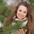 Portrait of happy young woman near spruce in winter outdoors — Stock Photo
