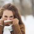 Young woman hiding in winter jacket outdoors — Stock Photo