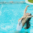 Happy young woman splashing water in pool — Stock Photo
