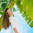 Happy young woman among tropical palms — Stock Photo