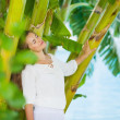 Relaxed young woman among tropical palms — Stock Photo