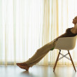 Silhouette of young woman relaxing in modern chair — Stockfoto