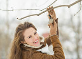 Smiling young woman hanging bird feeder on tree in winter park — Foto Stock
