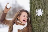 Happy young woman playing in snowball fights — Stock Photo