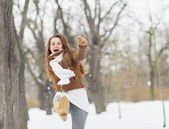 Happy young woman hitting snow with leg — Stock Photo