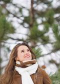 Glad ung kvinna som tittar upp på kopia utrymme i vinterparken — Stockfoto