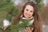 Portrait of happy young woman near spruce in winter outdoors — Stok fotoğraf