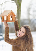 Smiling young woman hanging bird feeder on tree in winter outdoo — Stock Photo