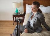 Donna d'affari, seduta sul letto nella camera d'albergo — Foto Stock