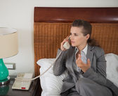 Business woman talking phone in hotel room — Stock Photo