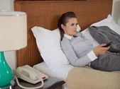 Tired business woman watching tv in hotel room — Stock Photo