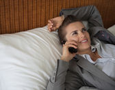 Business woman talking cell phone on bed in hotel room — Stock Photo